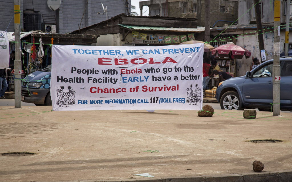 A banner encouraging people suffering from Ebola to go immediately to a health center for treatment is seen on a sidewalk in the city of Freetown, Sierra Leone, Thursday.  (Michael Duff / The Associated Press )