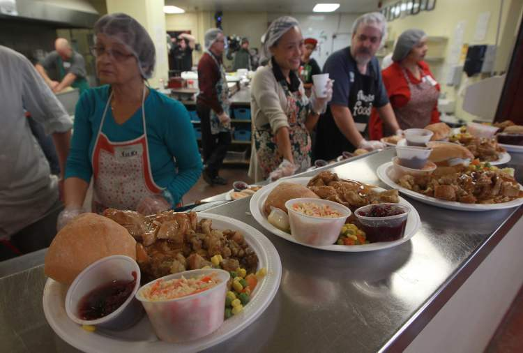 Volunteers prepare Siloam Mission's Christmas lunch Monday. (Joe Bryksa / Winnipeg Free Press)