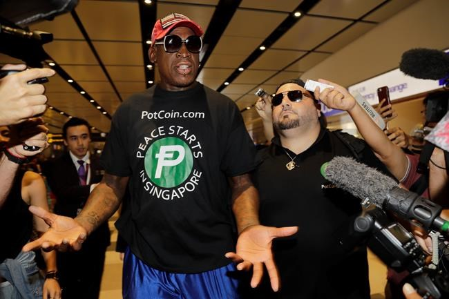 Dennis Rodman, centre, arrives at Singapore's Changi Airport on Tuesday.