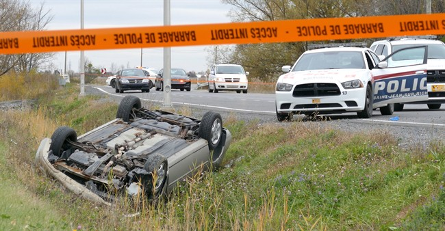 A car is overturned in the ditch in a cordoned off area in St-Jean-sur-Richelieu, Que. on Monday Oct. 20, 2014. One of two soldiers hit by a car on Monday in Saint-Jean-sur-Richelieu, Que., died of his injuries early Tuesday, according to Quebec provincial police. THE CANADIAN PRESS/Pascal Marchand
