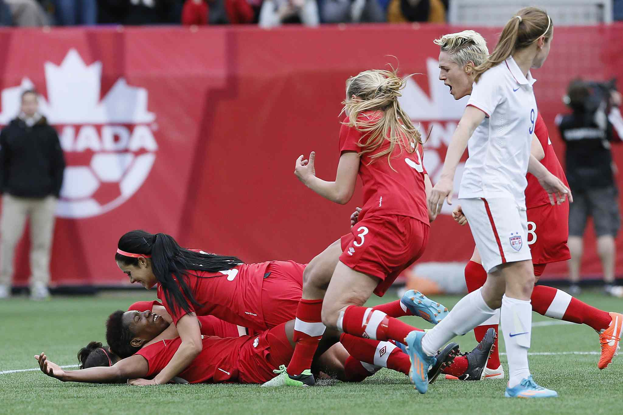 Canada's defender Kadeisha Buchanan (#20) celebrates her goal with forward Jonelle Filigno (16) and her team as USA's midfielder Heather O'Reilly (9) looks on during first the friendly match in Winnipeg.
