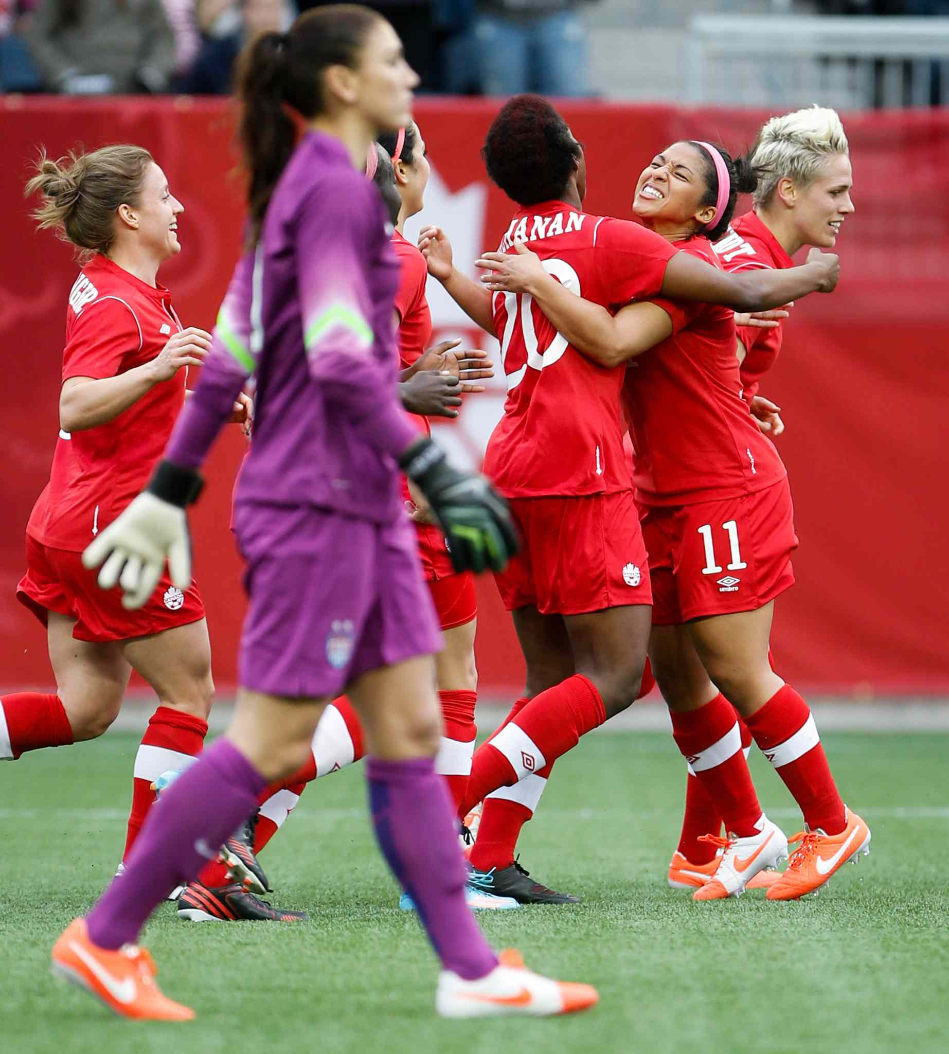 Canada midfielder Desiree Scott (11), hugs defender Kadeisha Buchanan (20) after Buchanan's goal as USA goalie Hope Solo looks on.