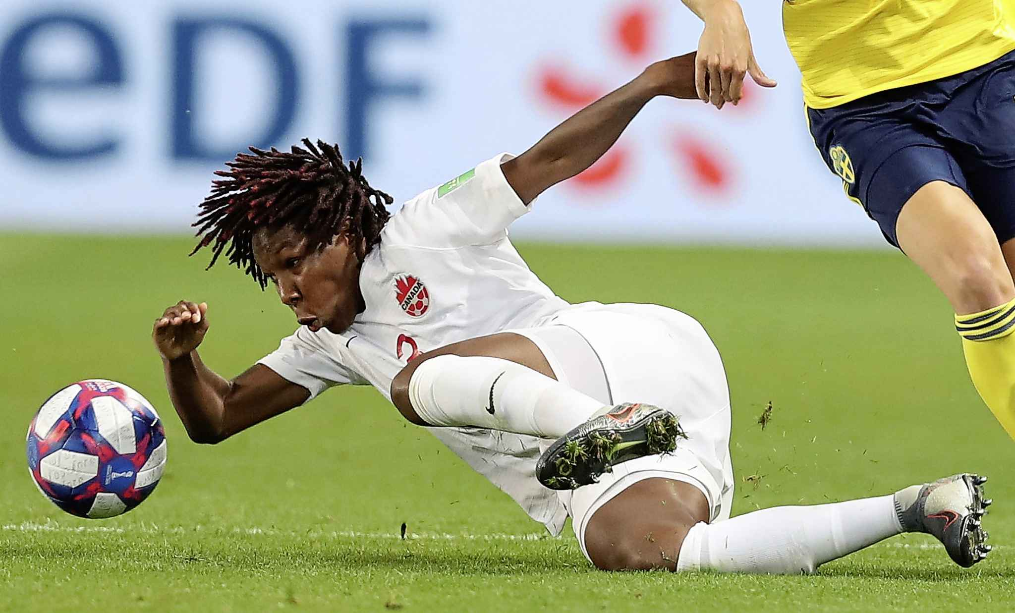 Canada's Kadeisha Buchanan, left, falls after challenging during the Women's World Cup against Sweden Monday.