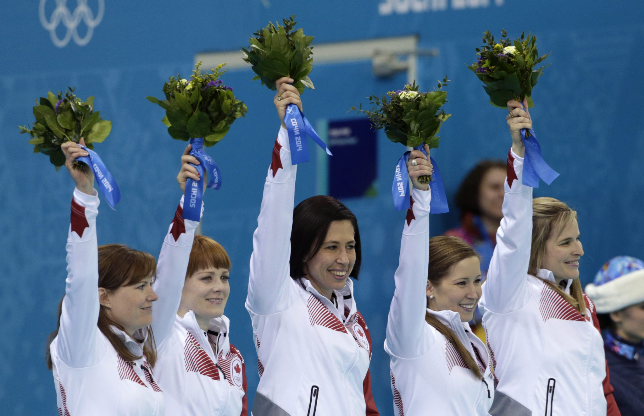 Canada's gold medal winning curling team, from left, Kirsten Wall, Dawn McEwen, Jill Officer, Kaitlyn Lawes, and skip Jennifer Jones raise their arms during the flower ceremony today after defeating Sweden in women's curling at the 2014 Winter Olympics in Sochi, Russia.