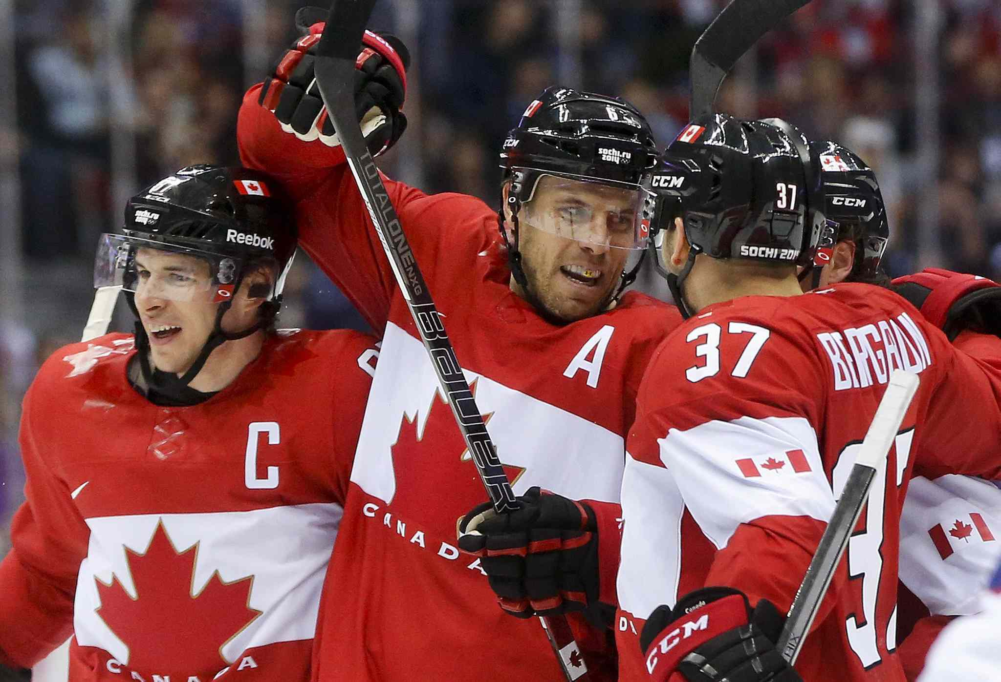 Canada defenceman Shea Weber, center, celebrates with forward Sidney Crosby, left, and forward Patrice Bergeron after scoring a goal against Norway.