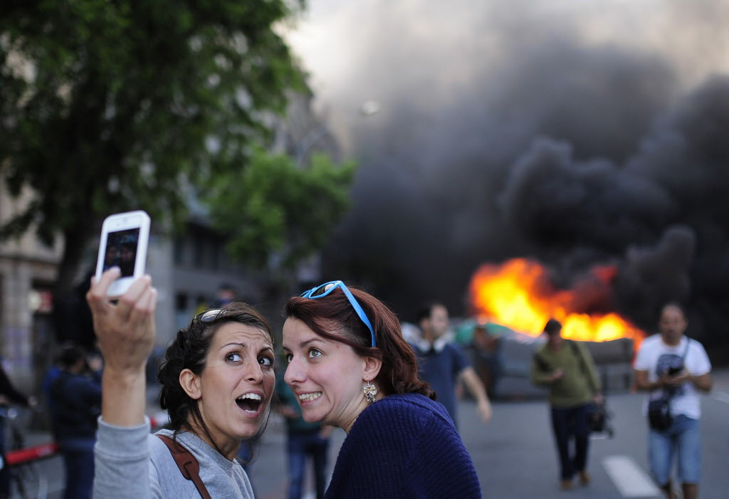 Tourists take a 'selfie' picture as demonstrators burn a trash container during a May Day rally in Barcelona, Spain on Thursday. Tens of thousands of workers marked May Day in European cities with a mix of anger and gloom over austerity measures imposed by leaders trying to contain the Eurozone's intractable debt crisis.  (Manu Fernandez / The Associated Press)