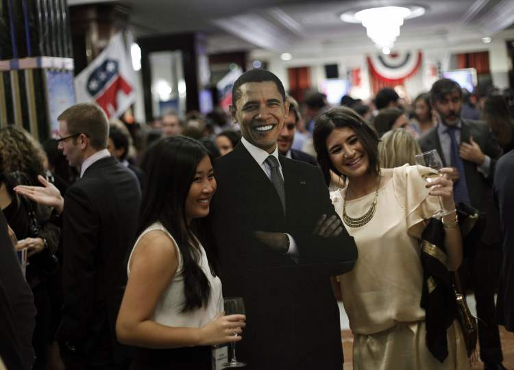 People pose with a picture of President Barack Obama during the Election Night Party 2012 following the U.S. Presidential Election, at the Intercontinental Hotel in Madrid, Spain, Wednesday.
