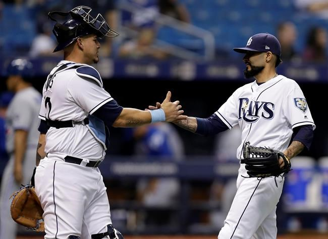 Tampa Bay Rays starting pitcher Sergio Romo and catcher Wilson Ramos celebrate after the Rays defeated the Toronto Blue Jays 4-1 in a baseball game Tuesday, June 12, 2018, in St. Petersburg, Fla. (AP Photo/Chris O'Meara)