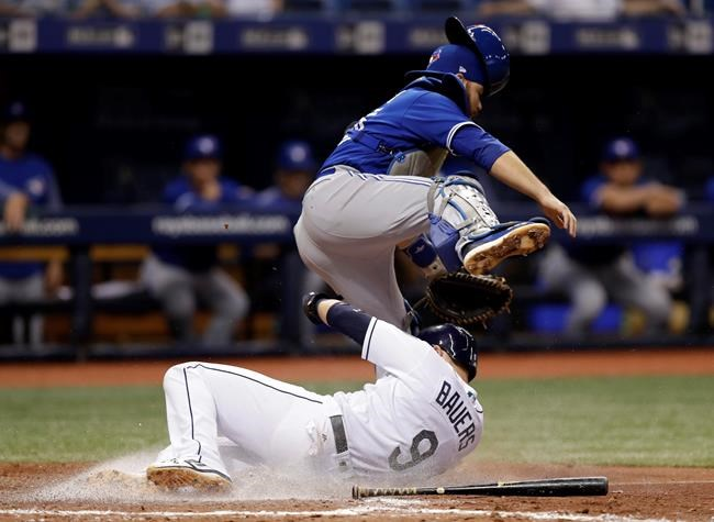 Tampa Bay Rays' Jake Bauers (9) slides in safely under Toronto Blue Jays catcher Russell Martin on a fielder's choice by Joey Wendle during the seventh inning of a baseball game Monday, June 11, 2018, in St. Petersburg, Fla. (AP Photo/Chris O'Meara)