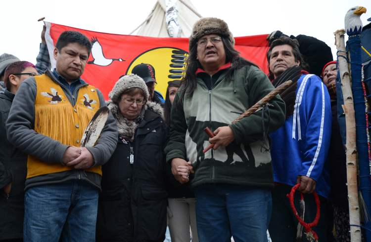 Attawapiskat Chief Theresa Spence stands with fellow hunger strikers Jean Sock (right in blue), Raymond Robinson, (second from right), and supporter Danny Metatawabin (left), during a news  conference outside her teepee near Parliament Hill earlier this month.