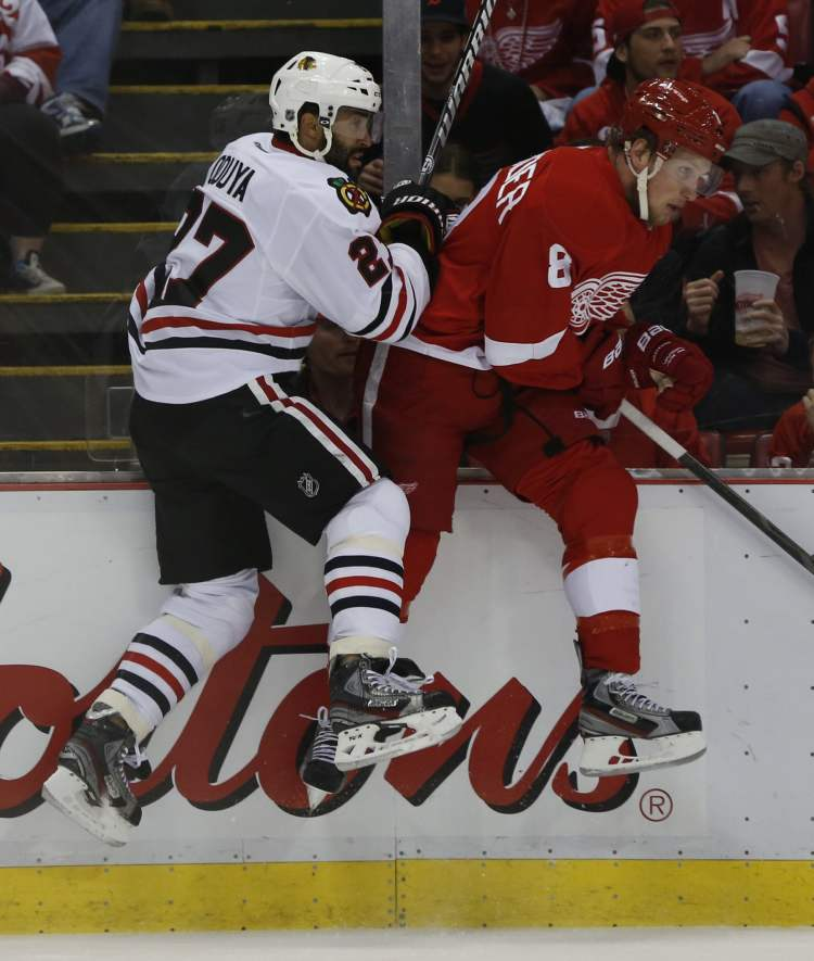 Detroit Red Wings' Justin Abdelkader and Chicago Blackhawks' Johnny Oduya both leave their feet as they battle on the boards during first-period action. (Julian H. Gonzalez / Detroit Free Press / MCT)
