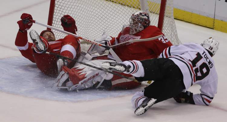 Detroit Red Wings' Johan Franzen tangles with Chicago Blackhawks' captain Jonathan Toews in front of Detroit goalie goalie Jimmy Howard during first-period action.