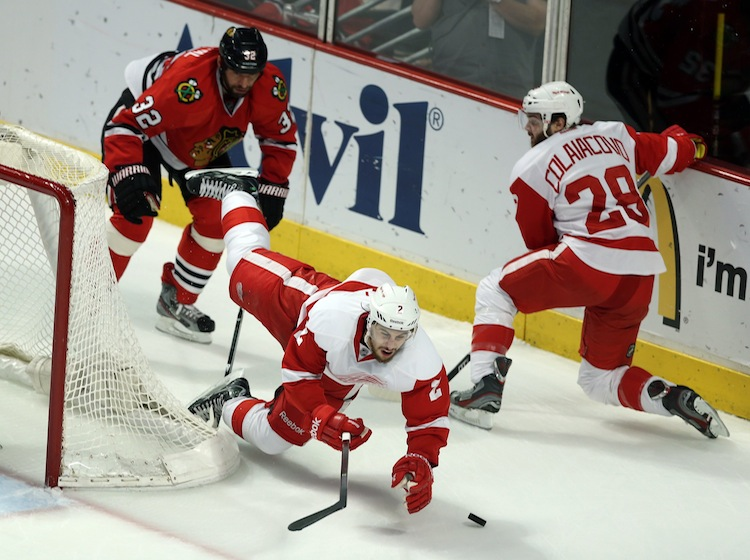 The Chicago Blackhawks' Michal Rozsival (left) trips up Brendan Smith of the Detroit Red Wings during the first period.