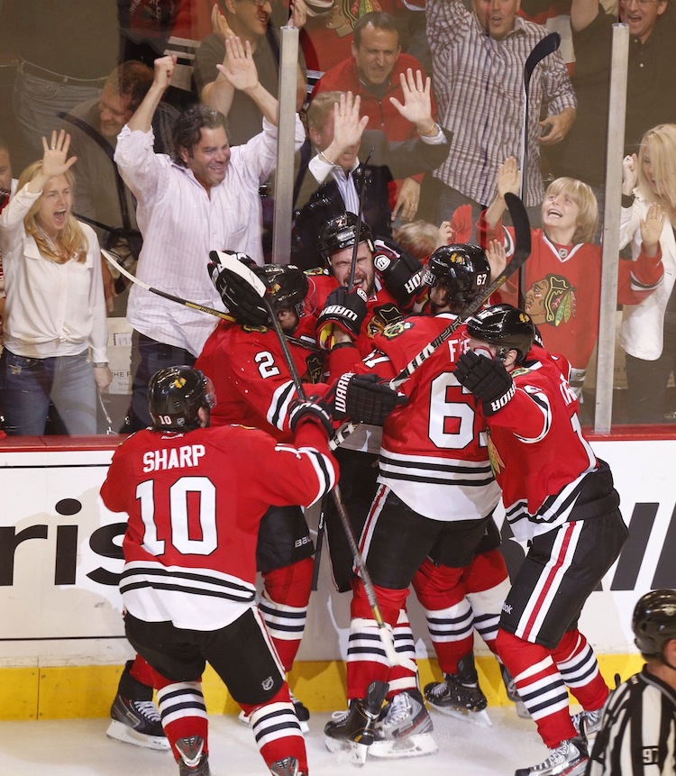 Brent Seabrook (center) is mobbed by teammates after scoring in overtime, eliminating the Detroit Red Wings and sending the Chicago Blackhawks to the Western Conference final. (Julian H. Gonzalez / Detroit Free Press / MCT)
