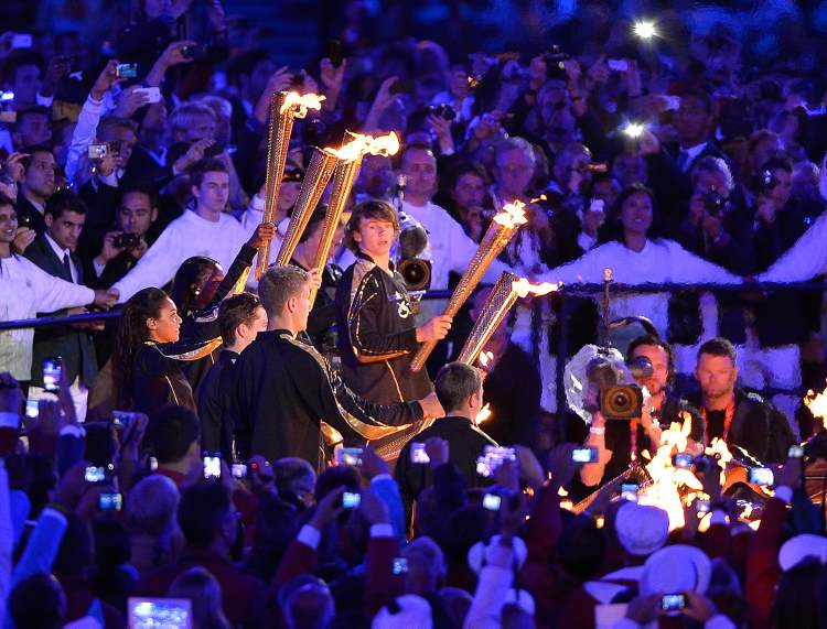 Seven young athletes hold their torches as they light the Olympic flame during the opening ceremony for the 2012 Olympic Games in London on Friday. (Tribune Media MCT)