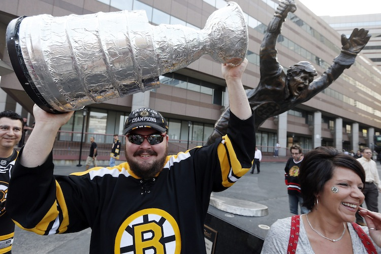 Brian Rogers holds a replica Stanley Cup beside a statue of Boston Bruins' legend Bobby Orr outside TD Garden before the game. (Michael Dwyer / The Associated Press)