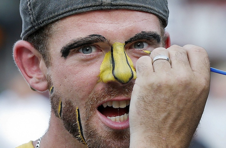Barry Hale (right) paints the face of his brother Jake Pickard before the game. (Michael Dwyer / The Associated Press)
