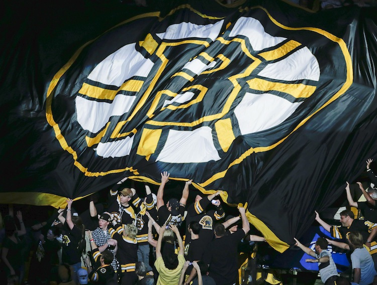 Boston Bruins fans pass an over-sized Bruins flag through the stands.