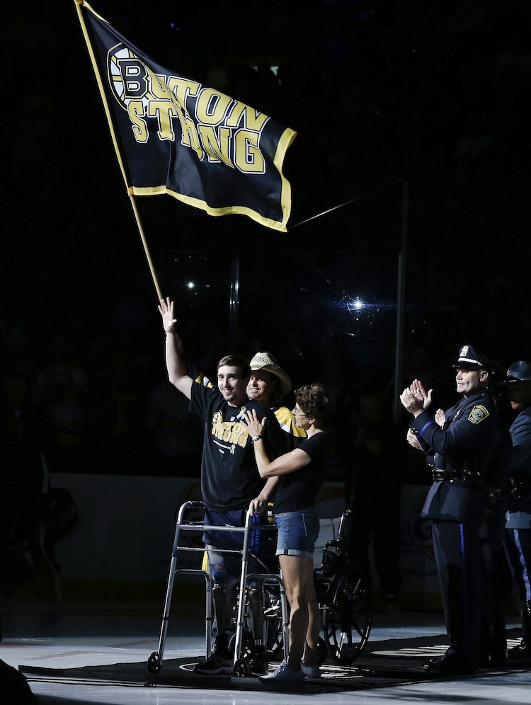 Standing on artificial legs, Boston Marathon bombing victim Jeff Bauman and Carlos Arredondo (in hat), who assisted him at the scene, waves the Boston Strong banner before Game 6. (Elise Amendola / The Associated Press)