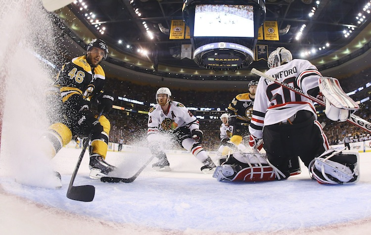Boston Bruins center David Krejci and Chicago Blackhawks defenceman Duncan Keith rush the net in front of Blackhawks goalie Corey Crawford during the first period. (Harry How / The Associated Press)