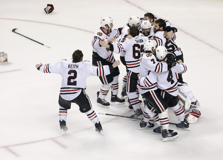 The Chicago Blackhawks celebrate after the horn sounds to end the game. The score: 3-2 Blackhawks. (Charles Krupa / The Associated Press)