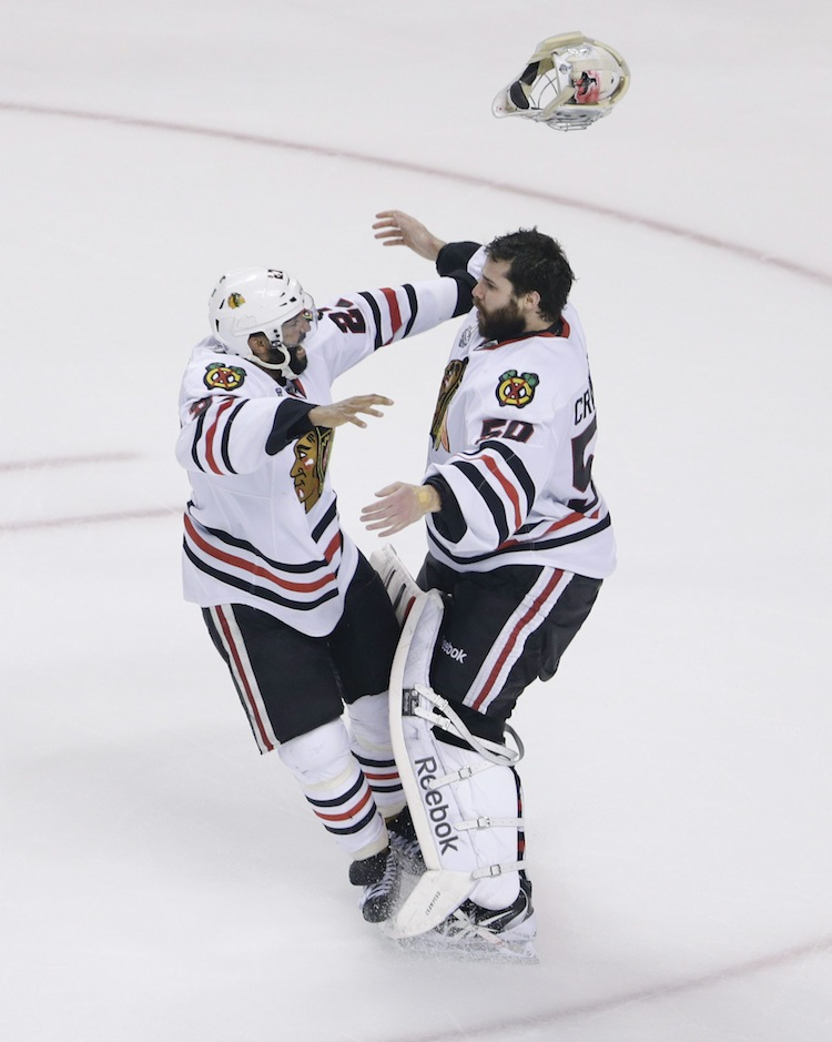 Chicago Blackhawks defenseman Johnny Oduya (left) hugs Chicago Blackhawks goalie Corey Crawford  after winning Game 6 and the Stanley Cup.