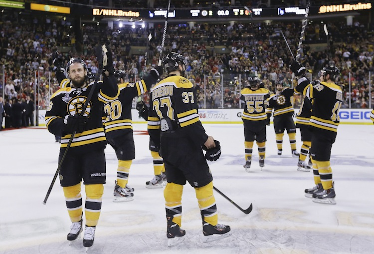 Boston Bruins centers Rich Peverley (left), Patrice Bergeron (37) and teammates salute  the fans. (Elise Amendola / The Associated Press)