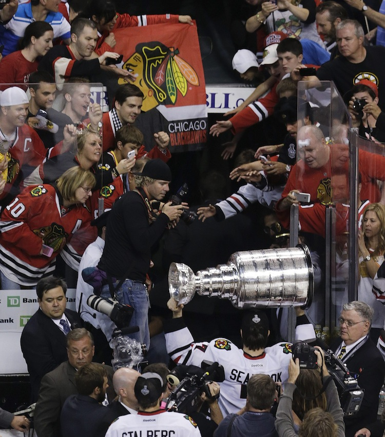 Chicago Blackhawks defenceman Brent Seabrook carries the Stanley Cup off the ice amid Blackhawks fans after Chicago beat the Boston Bruins 3-2 in Game 6 of the Stanley Cup Finals Monday. (Charles Krupa / The Associated Press)