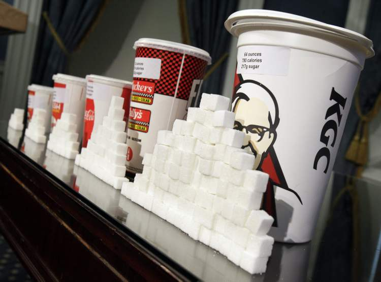A display of various sizes of soft-drink cups next to stacks of sugar cubes at a news conference at New York's City Hall in 2012. New research greatly strengthens the case against soda and other sugary drinks as culprits in the obesity epidemic.