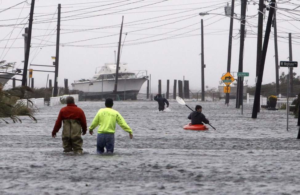People wade and paddle down a flooded street as Hurricane Sandy approaches in Lindenhurst, N.Y. Gaining speed and power through the day, the storm knocked out electricity to more than 1 million people and figured to upend life for tens of millions more. (AP Photo/Jason DeCrow)