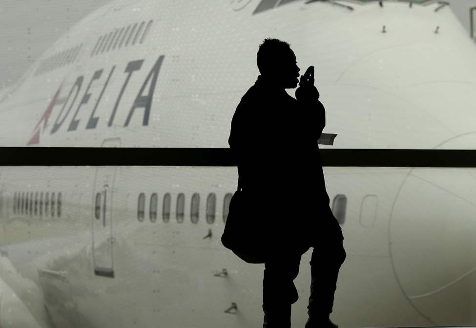 A traveler on Delta Airlines waits for her east-bound flight in Detroit (AP Photo/Charlie Riedel)