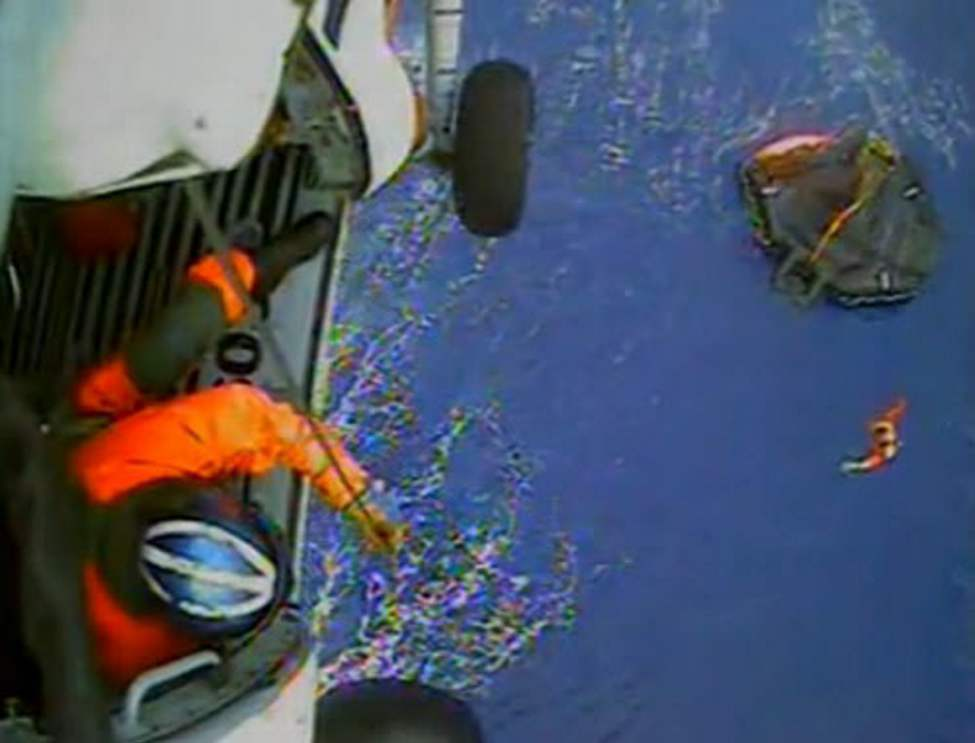 In this image made from video and released by the U.S. Coast Guard, a USCG rescue swimmer, in water at right, and a crew member use a hoist to bring up a survivors into a helicopter. A replica tall ship caught in Hurricane Sandy's wrath began taking on water, forcing the crew to abandon the boat Monday in rough seas off the North Carolina coast. The Coast Guard rescued 14 crew members by helicopter, but two people were still missing. (AP Photo/U.S. Coast Guard) (CP)