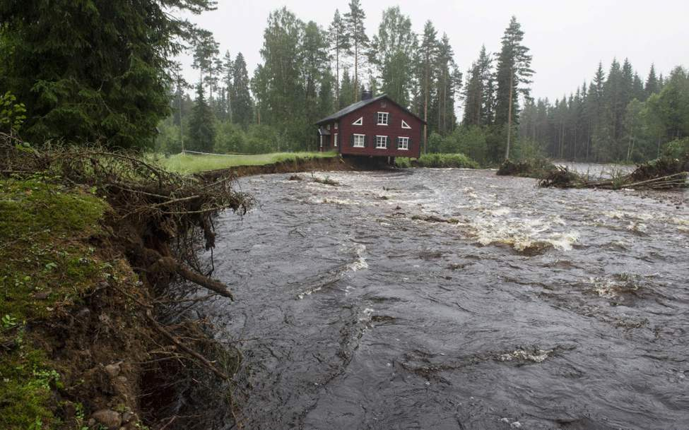 A house, with part of its foundation eaten away, hangs over a rain-swollen creek at Nyhammar in Dalarna, central Sweden. Areas in Sweden hit by floods are bracing themselves for further downpours and thunderstorms as a low pressure system moves across the region. (AP Photo/Leif R Jansson)