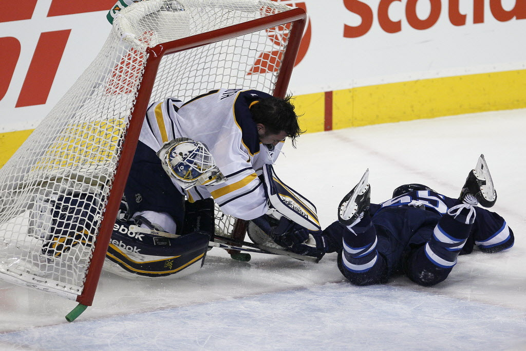 Winnipeg Jets' Mark Scheifele (#55) crashes into Buffalo Sabres' goaltender Jhonas Enroth (#1) during second period at the MTS Centre Tuesday. (John Woods / Winnipeg Free Press)