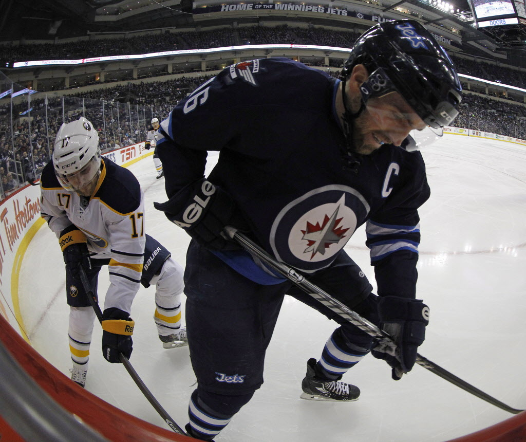 Winnipeg Jets' Andrew Ladd, right, and Buffalo Sabres' Linus Omark battle for the puck during the game's second period Tuesday. (Trevor Hagan / The Canadian Press)