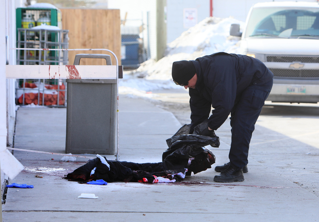 An investigator examines blood-stained clothing at the scene near a 7-Eleven. (Ruth Bonneville / Winnipeg Free Press)