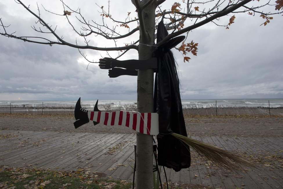 A Halloween decoration of a witch blown into a tree sits beside Lake Ontario as waves driven by superstorm Sandy crash on a beach in Toronto on Tuesday morning. (The Canadian Press / Frank Gunn)