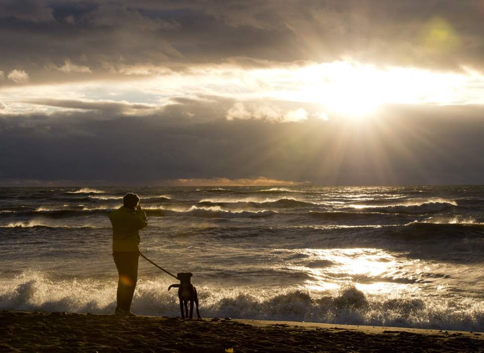 A woman photographs the sunrise as waves driven by superstorm Sandy crash on a beach in Toronto on Tuesday morning.  (The Canadian Press / Frank Gunn)