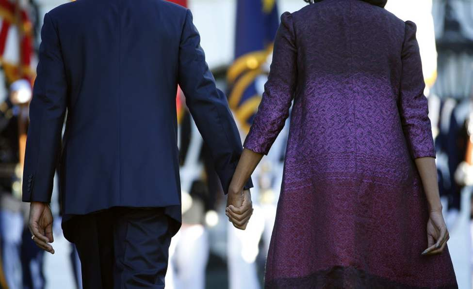 President Barack Obama and first lady Michelle Obama hold hands as they walk back to the White House in Washington, after joining members of the White House staff during a moment of silence to mark the 11th anniversary of the Sept, 11th. (AP Photo/Carolyn Kaster)