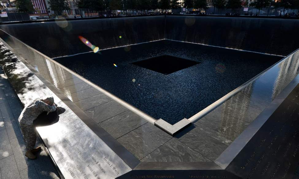 Scott Willens, who joined the United States Army three days after the attacks on Sept. 11, 2001, pauses by the South Pool of the World Trade Center Memorial during the 11th anniversary observance in New York. (AP Photo/Justin Lane, Pool)