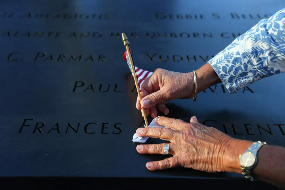 Judy Parisio places a small U.S. flag on the engraved name of her niece, Frances Ann Cilente who worked and died at the World Trade Center, during the commemoration ceremony of the 11th anniversary of the Sept. 11, 2001 terrorist attacks by the North Pool at World Trade Center in New York. (AP Photo/The New York Times, Chang W. Lee, Pool)