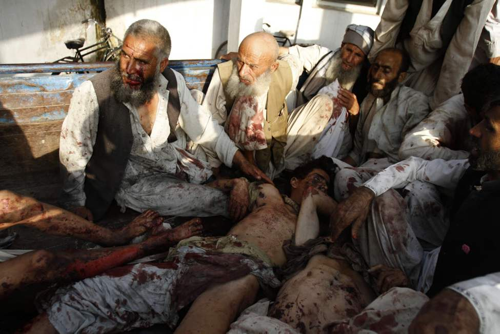 Injured Afghan men arrive at a hospital in the back of a truck, along with the dead bodies of other victims, after a suicide attack on a funeral in Durbaba district of Jalalabad, east of Kabul. Afghan officials say a suicide bomber has killed several civilians and wounded dozens more at a funeral for a village elder in a remote part of eastern Afghanistan. The deputy police chief for Nangarhar province, Jamil Shamal, says the attack took place on Tuesday in the village of Shagai in the Durbaba district.(AP Photo/Rahmat Gul)