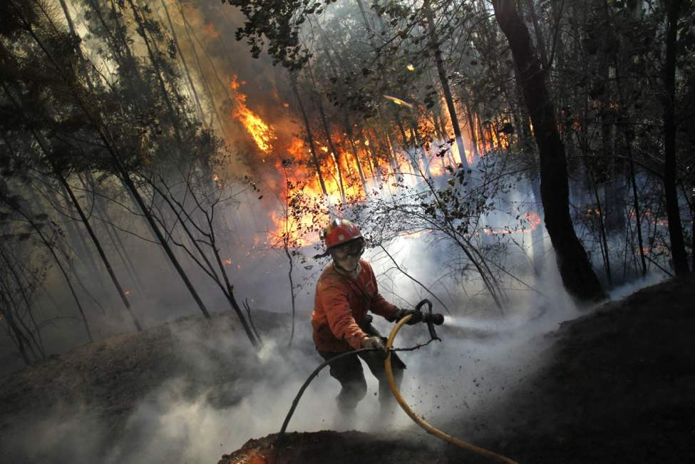 A firefighter steps back while working to douse a fire in Alvaiazere, center Portugal. A Portuguese official says authorities have asked other European countries to send help as the country's firefighters struggle to contain forest blazes being fueled by high temperatures and strong winds. More than 1,700 firefighters, almost 500 vehicles and 13 aircraft fought blazes mostly in the north of the country. (AP Photo/Francisco Seco)