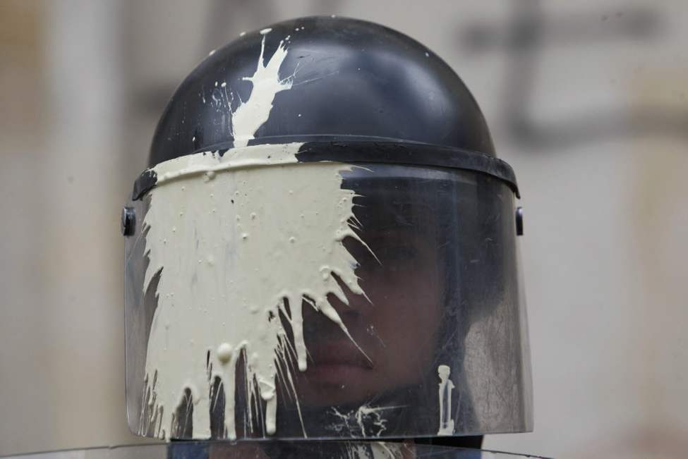 A riot police officer with his masked stained with paint thrown by students watches a march by teachers and students protesting a wide range of issues regarding the government's educational policies in Bogota, Colombia. (AP Photo/William Fernando Martinez)