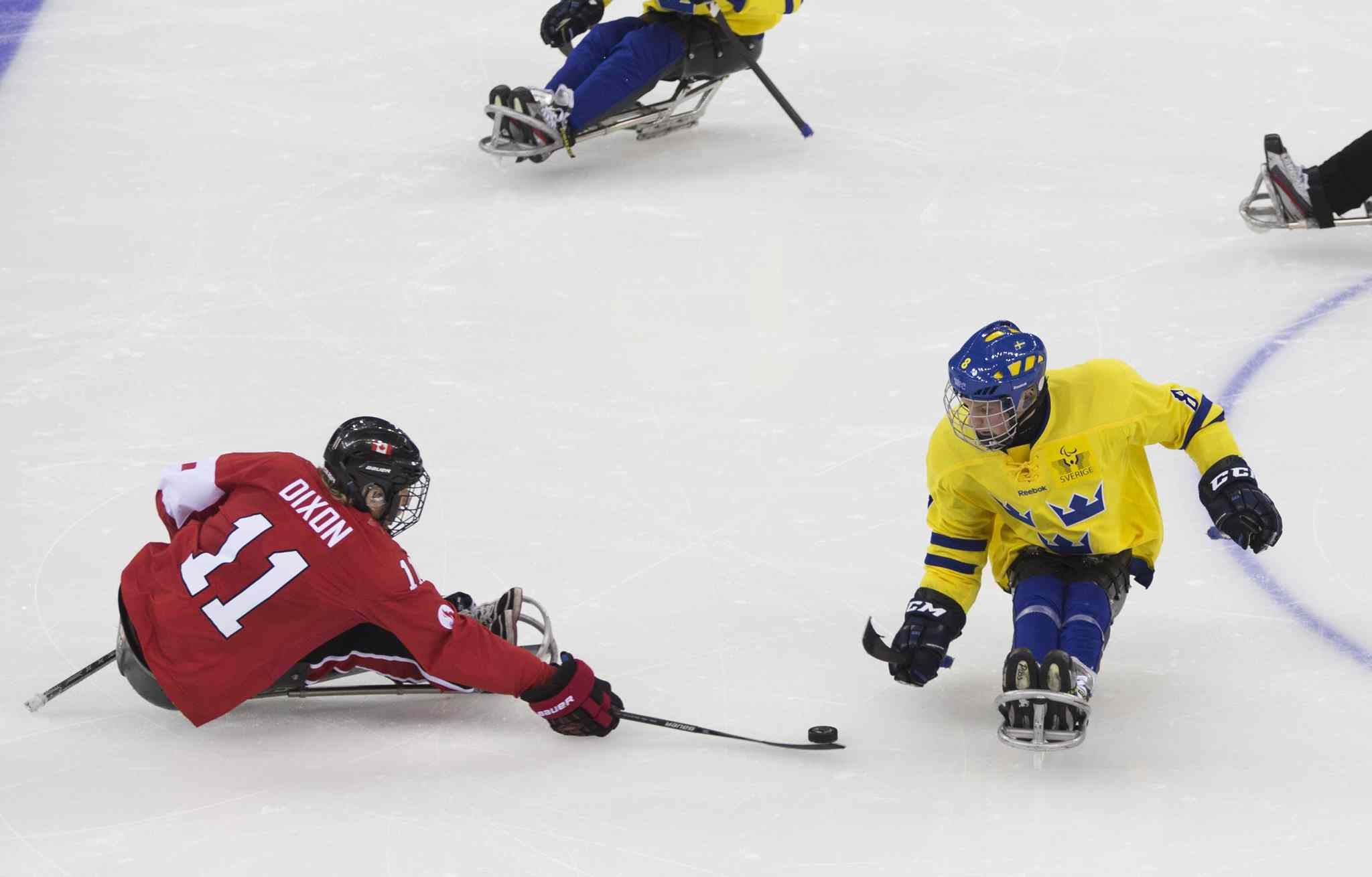 Adam Dixon of Canada, left, and Per Kasperi of Sweden, right, in action during the ice sledge hockey match at the Shayba Arena at the 2014 Winter Paralympics in Sochi, Russia, Saturday, March 8, 2014.