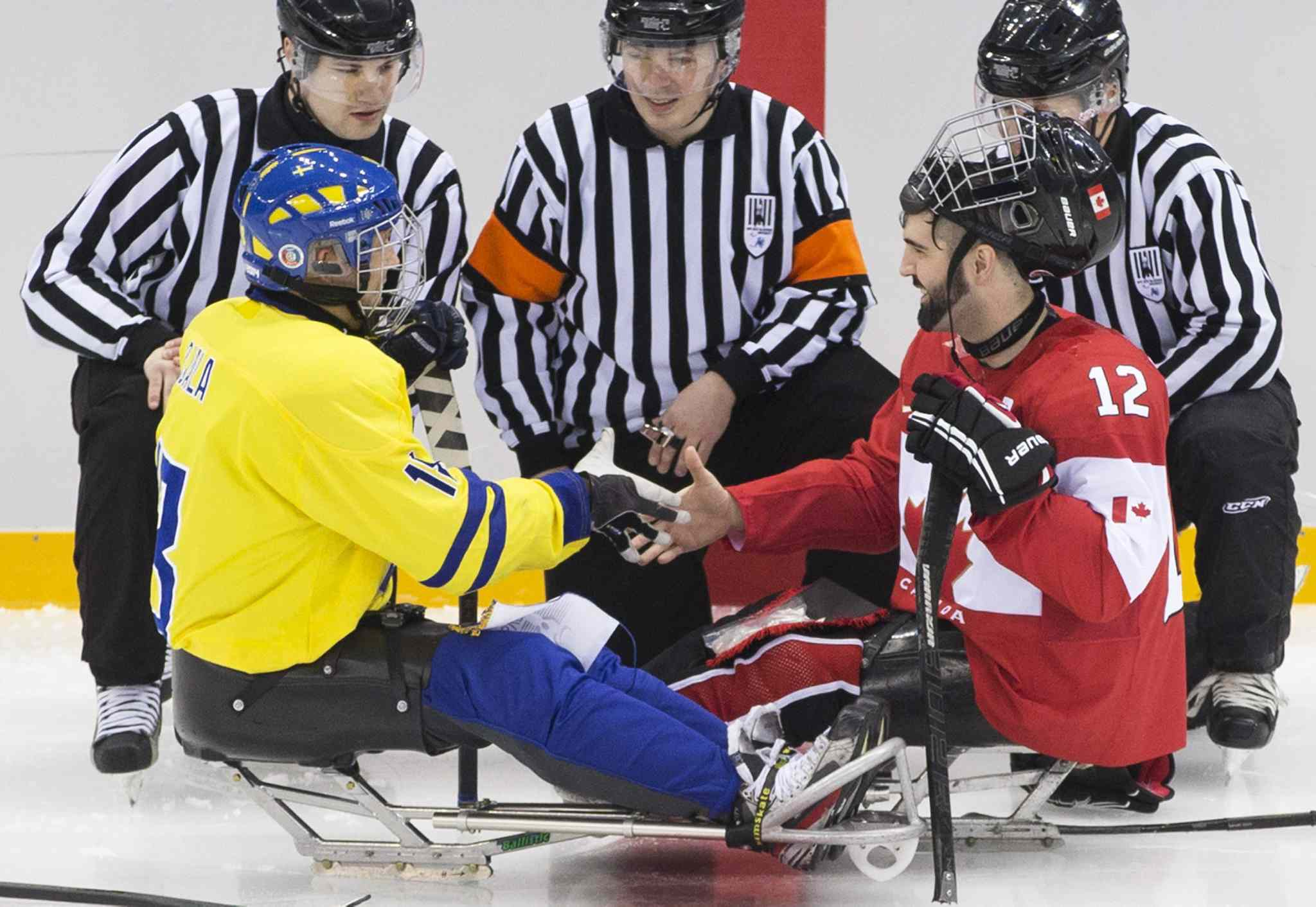 Greg Westlake of Canada, right, and Peter Ojala of Sweden, left, shake hands before the ice sledge hockey match at the Shayba Arena at the 2014 Winter Paralympics in Sochi, Russia, Saturday, March 8, 2014.