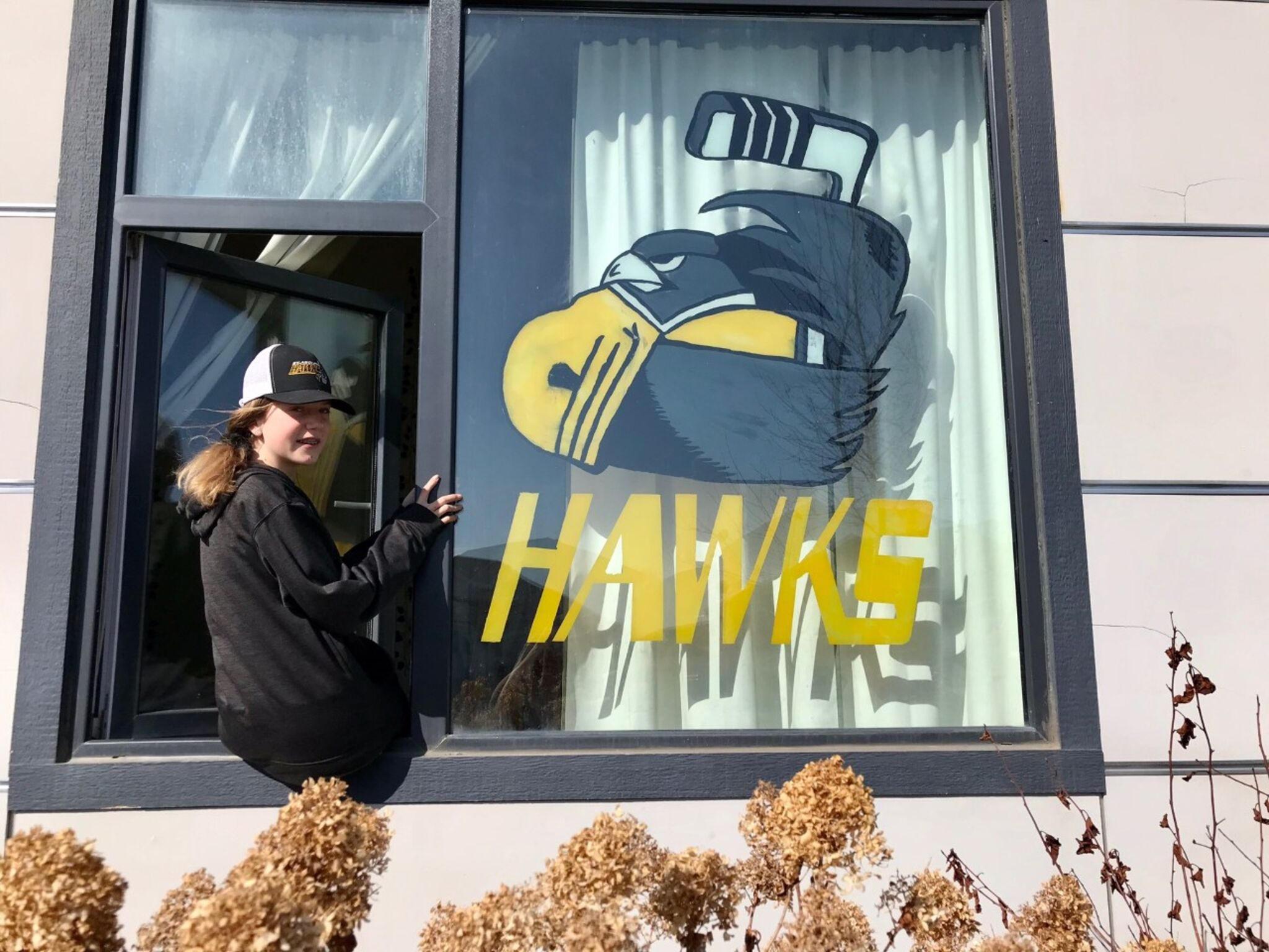 Twelve-year-old Arianne Ziegler with the artwork she painted on a window at their St. Adolphe home.