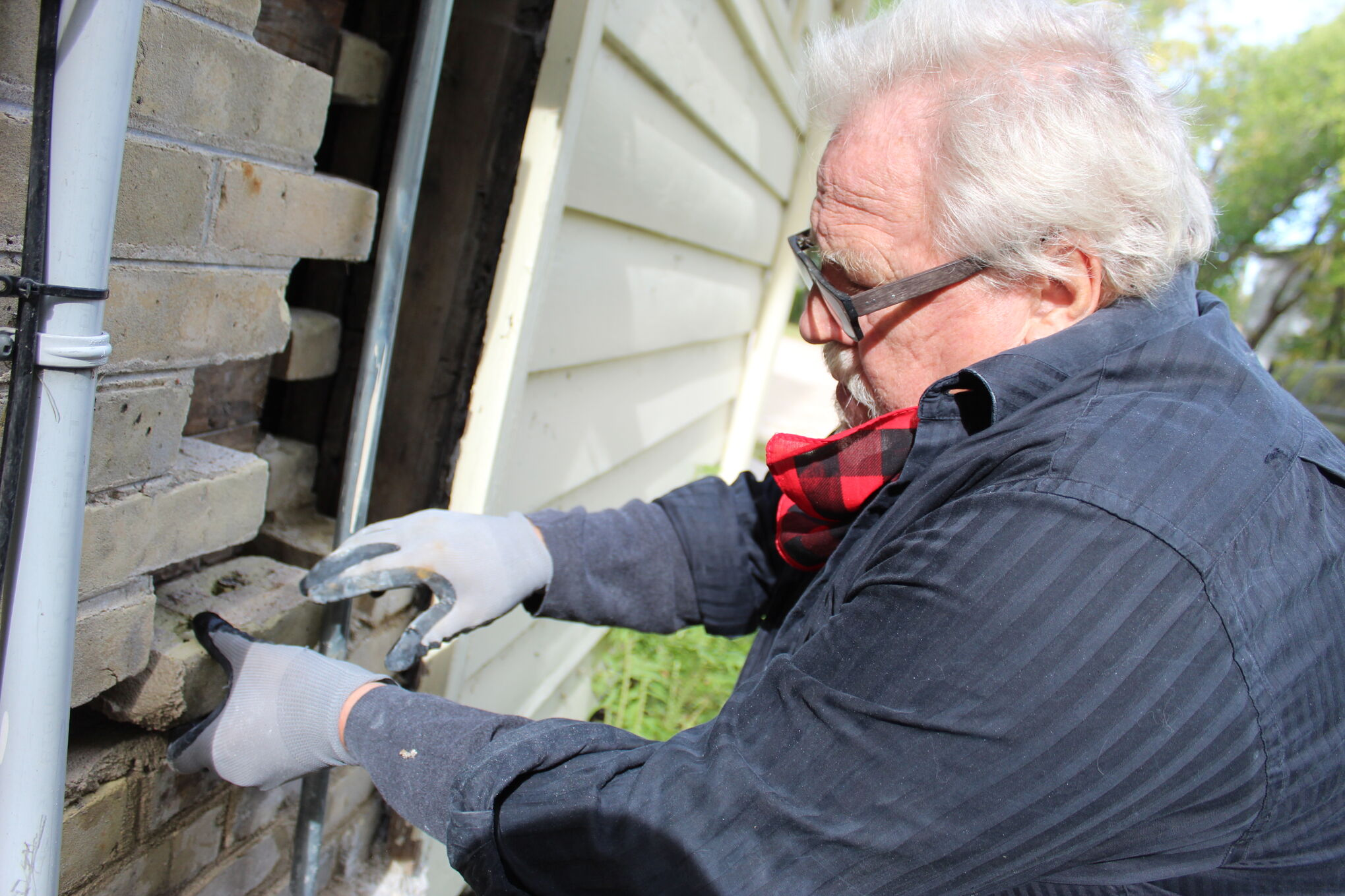 """Ernést Hiebert repairs the deteriorating brick façade of the St Pierre Museum. """"I love doing it. I can hear by dad,"""" he says of his restoration work."""