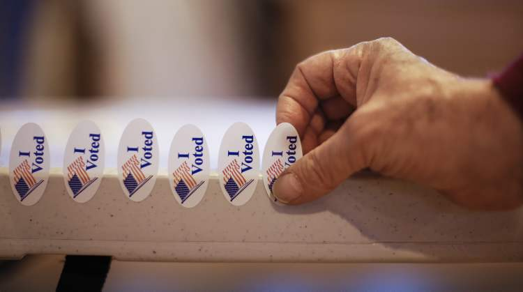 Poll worker Leon Levy attaches stickers to a tabletop on election day on Tuesday, in Nashville, Tenn. After a grinding presidential campaign President Barack Obama and Republican presidential candidate, former Massachusetts Gov. Mitt Romney, yield centre stage to American voters Tuesday for an Election Day choice that will frame the contours of government and the nation for years to come.