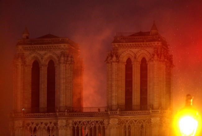 Flames illuminate the night sky as Notre Dame cathedral burns in Paris, Monday, April 15, 2019. Massive plumes of yellow brown smoke is filling the air above Notre Dame Cathedral and ash is falling on tourists and others around the island that marks the center of Paris. (AP Photo/Thibault Camus)